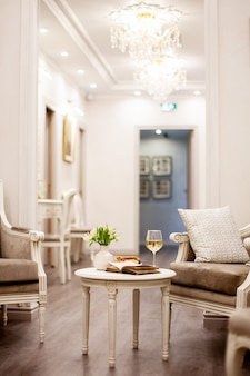 Um vaso com lindas flores brancas, um copo de vinho e bolos crocantes fica em cima da mesa em uma sala iluminada e aconchegante. tiro no interior
