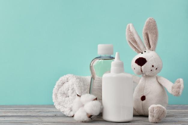 Um vaso com óleo, um frasco de xampu, talco e um coelho em uma prateleira de madeira