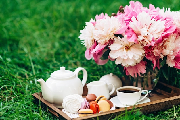 Um vaso com peônias, um bule e uma xícara de chá em uma bandeja