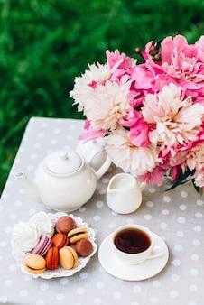 Um vaso com peônias, um bule e uma xícara de chá na mesa
