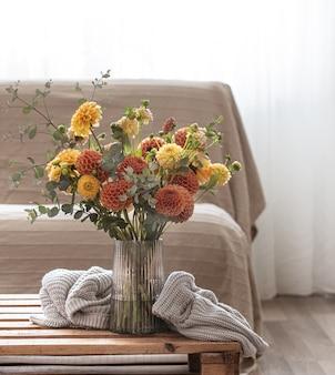 Um vaso com um buquê de crisântemos amarelos e laranja sobre uma mesa com um elemento de malha no interior da sala.