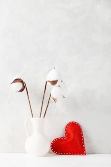 Um vaso de algodão e um coração vermelho contra a luz de uma parede clara, um conceito, um postal de dia dos namorados.