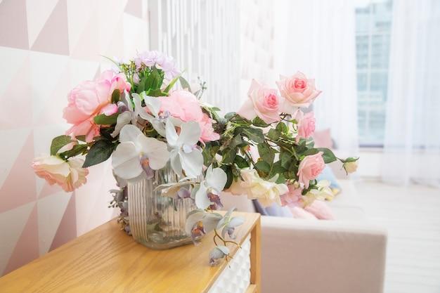 Um vaso de flores em uma cômoda perto da parede com um padrão geométrico em uma sala de estar rosa claro