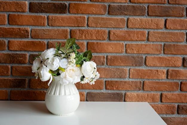Um vaso de flores em uma mesa branca com uma parede em estilo loft. foco seletivo suave.