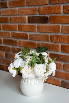 Um vaso de flores em uma mesa branca com uma parede em estilo loft