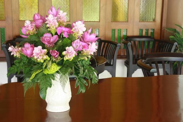 Um vaso de flores na mesa de madeira