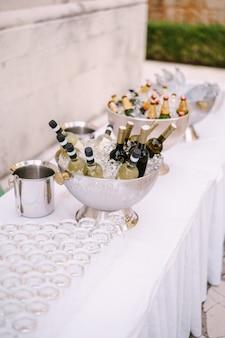 Um vaso de gelo em uma mesa com garrafas de álcool