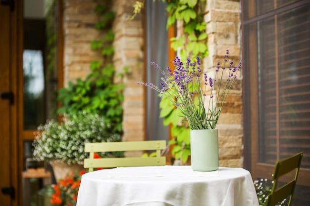 Um vaso de lavanda em uma mesa perto de uma casa de campo - elemento de exterior