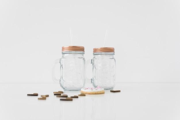 Um vazio dois frascos de pedreiro transparente com corações e cookie no fundo branco