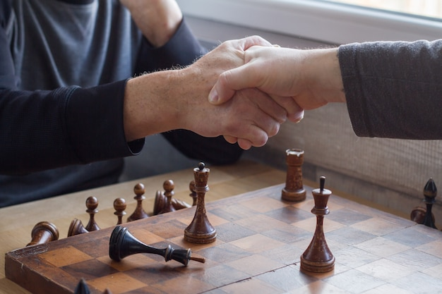 Um velho agita as mãos com um adversário em um jogo de xadrez