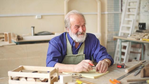 Um velho aprendiz senta-se à mesa de sua oficina e desenha um esboço de um produto de madeira