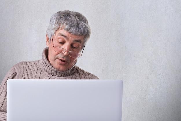Um velho avô de óculos, fazendo uma videochamada pelo laptop, comunicando-se com os filhos.