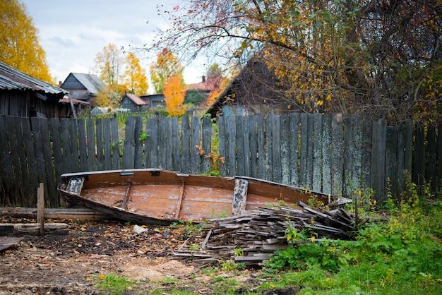 Um velho barco abandonado de madeira no chão e edifícios da vila em ruínas ao redor