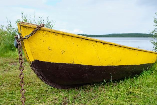 Um velho barco acorrentado na margem do lago no verão
