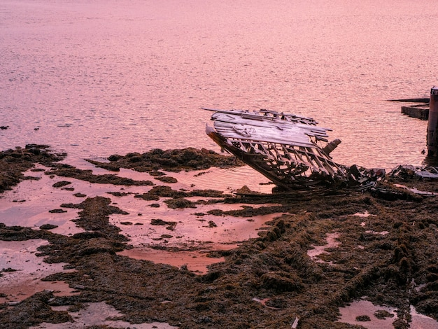 Um velho barco de pesca enferrujado abandonado por uma tempestade na costa. cemitério de navios. península de kola, teriberka, rússia.