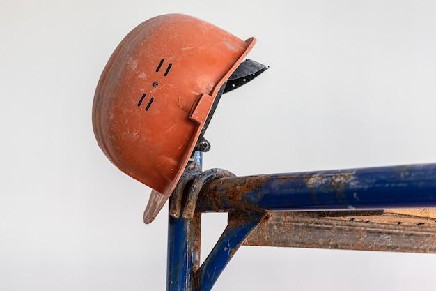 Um velho capacete de trabalho está pendurado no andaime. fundo desfocado. conceito de trabalho duro do construtor.