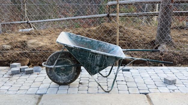 Um velho carrinho de mão verde metálico com uma roda e alças está em um canteiro de obras. dispositivo para transporte de mercadorias. consiste em uma carroceria de carga, uma ou mais rodas e uma alça.