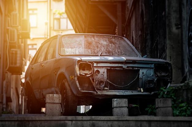 Um velho carro azul quebrado e enferrujado abandonado sem faróis e uma rachadura no pára-brisa
