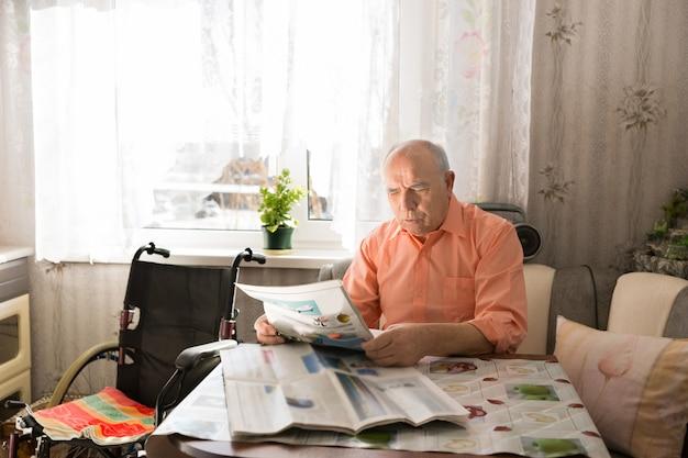 Um velho de camisa laranja lendo as manchetes do jornal na sala de estar com sua cadeira de rodas ao lado.