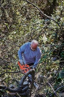 Um velho está cortando lenha no jardim de sua casa.