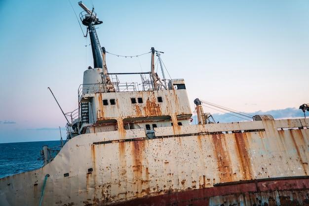 Um velho navio enferrujado encalhado está à beira-mar, de perto.