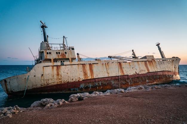 Um velho navio enferrujado encalhado está à beira-mar.