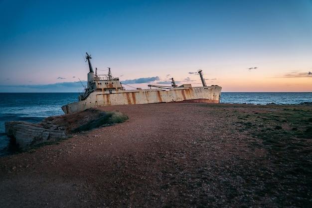 Um velho navio enferrujado encalhado está à beira-mar