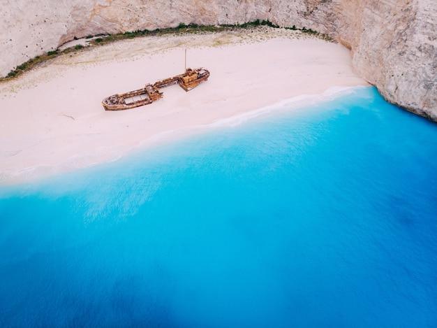 Um velho navio enferrujado, naufragado, repousa à beira-mar. navagio bay shipwreck beach grécia, zakynthos