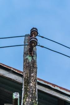 Um velho poste elétrico de madeira com céu azul