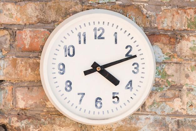 Um velho relógio branco contra a parede de tijolo resistiu