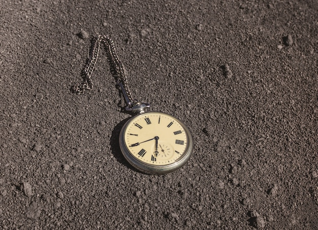 Um velho relógio de bolso está em solo seco. tempo passado e futuro.