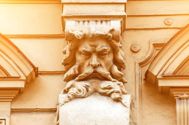 Um velho rosto de estuque de um homem com barba no prédio.