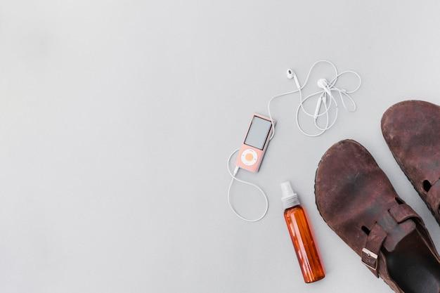 Um velho sapatos rústicos com frasco de perfume e mp3 player com fone de ouvido