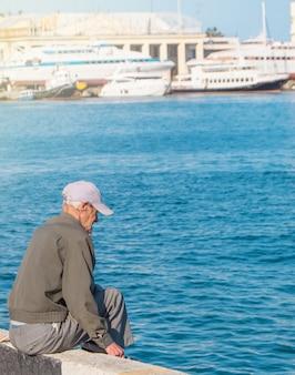 Um velho sentado na praia no cais e pesca, um dia ensolarado de verão, pensionista de lazer com um estilo de vida ativo