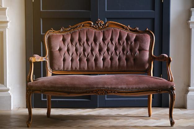 Um velho sofá antigo com furos no tecido fica perto da porta. sala de estar ou corredor interior