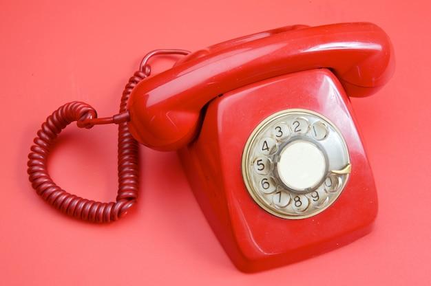 Um velho telefone vermelho sobre fundo vermelho