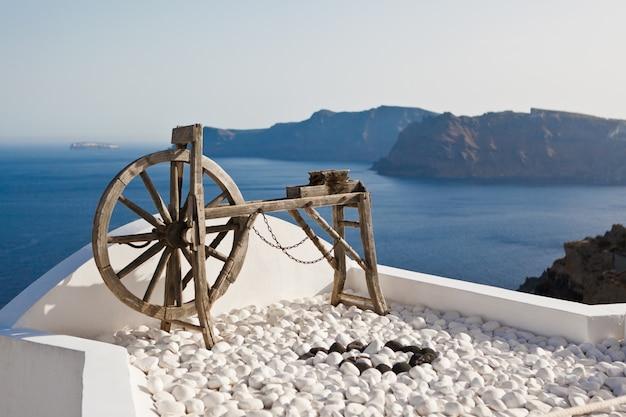 Um velho torno de fiação de madeira acima do oceano azul em santorini