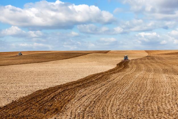 Um velho trator ara o solo em um campo enquanto prepara o campo para a semeadura, a paisagem na hora nublada do dia