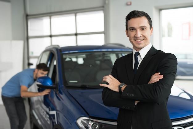 Um vendedor de carros está posando para uma câmera perto de compradores.