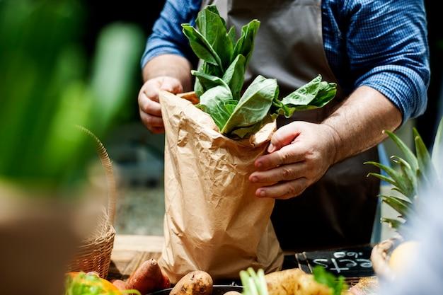Um, vendedor, pôr, vegetal, em, um, saco