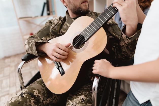 Um veterano em uma cadeira de rodas está tocando violão.
