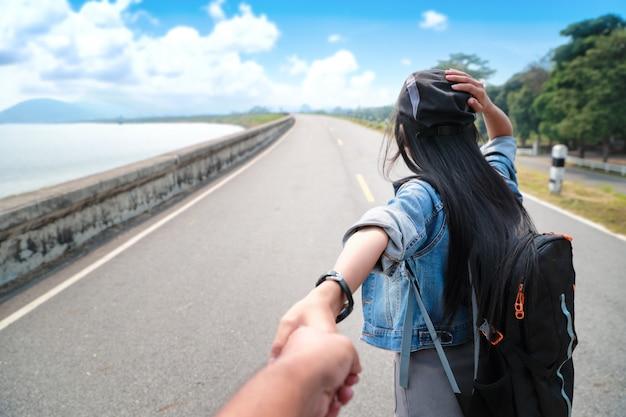 Um viajante asiático novo dos pares que guarda a mão com a trouxa ao viajar em férias do feriado