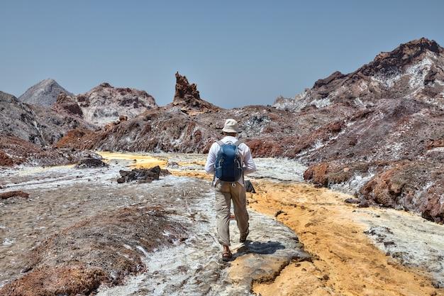 Um viajante caminhando ao longo do leito do rio amarelo.