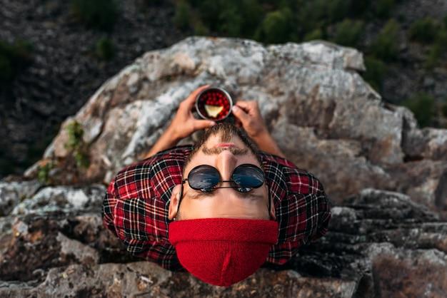 Um viajante com óculos de sol olha para a câmera. férias e conceito de turismo. retrato de um turista do sexo masculino à beira de uma montanha. retrato masculino no fundo de uma paisagem montanhosa. copie o espaço