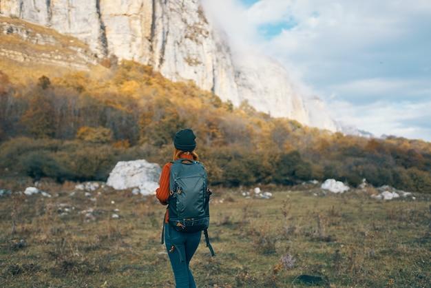 Um viajante com um suéter jeans com uma mochila nas costas e um chapéu quente nas montanhas