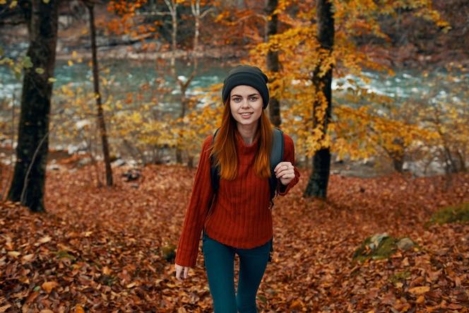 Um viajante com um suéter vermelho e um chapéu caminha na floresta de outono perto de uma vista do topo de um rio na montanha