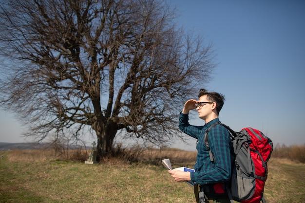 Um viajante com uma mochila, olhando para o mapa e andando na zona rural.