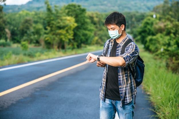Um viajante do sexo masculino com uma bolsa de ombro e olhando para o relógio.