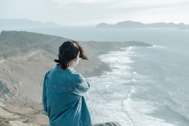 Um viajante em frente à costa selvagem espanhola usando uma máscara facial, conceito de bem-estar, vida e liberdade