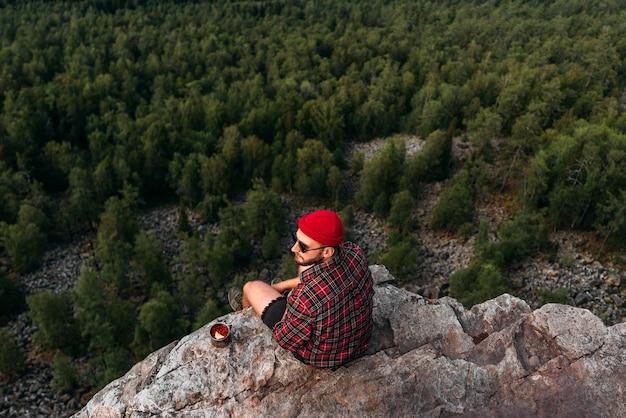 Um viajante está sentado em uma rocha com uma vista panorâmica da floresta. o conceito de recreação e turismo. um viajante sentado à beira de um penhasco. um homem desfruta de belas vistas. viajar por